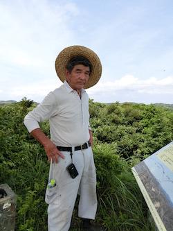 山頂を案内する渡辺俊彦さん