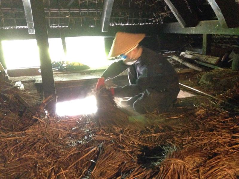 古民家屋根裏で使われなくなった茅を整理する永森さん