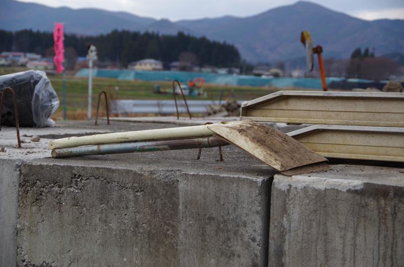 「復興の槌音2」:村内倉庫の改築が進行中。奥に見えるのは除染土の山