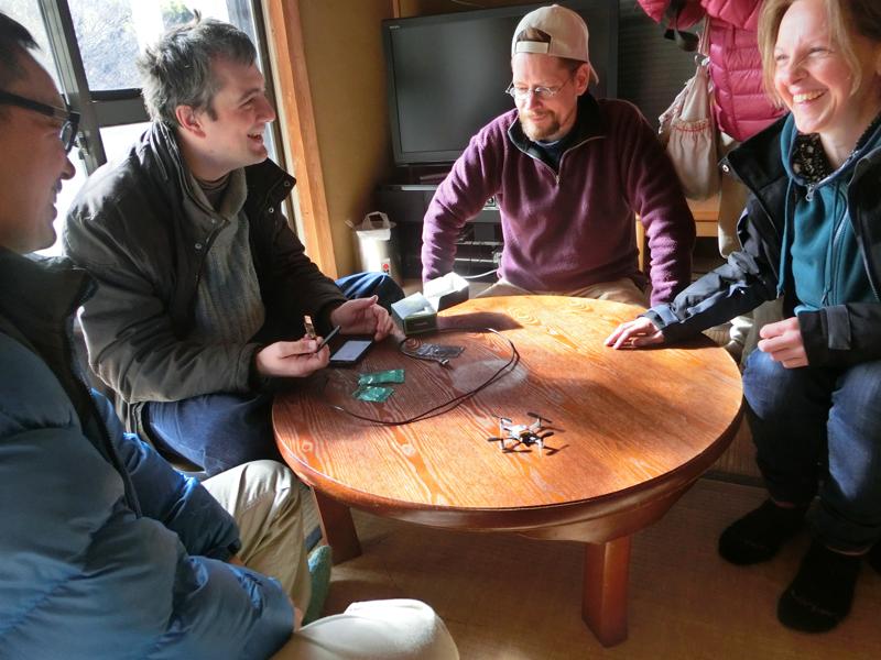 イブさん(左から2番目)の試作したスマートフォンで操作可能なクアッドコプターを囲んで談笑するハッカーファームの皆さん