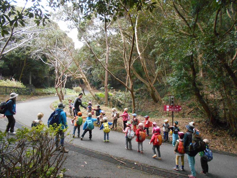 大房岬でマラソンの練習を行う大学生にハイタッチする「森のようちえんはっぴー」の子ども達