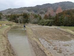 保水性をたかめるため田んぼ周りに土壁を作る「黒塗り」作業中の五十嵐さん