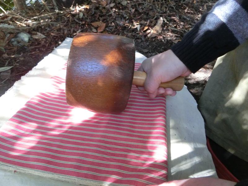 織り上がった反物は、一枚岩の上で約半日木槌で打ち込まれ、絹のような艶に仕上がる(砧打ち)