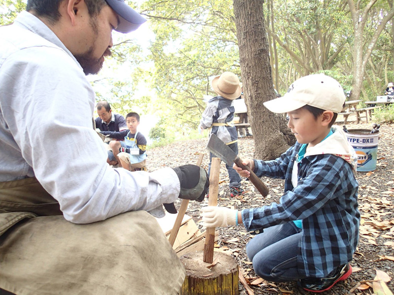 火をおこ着火材を作るため、小学生に鉈(なた)の使い方を指導する神保所長
