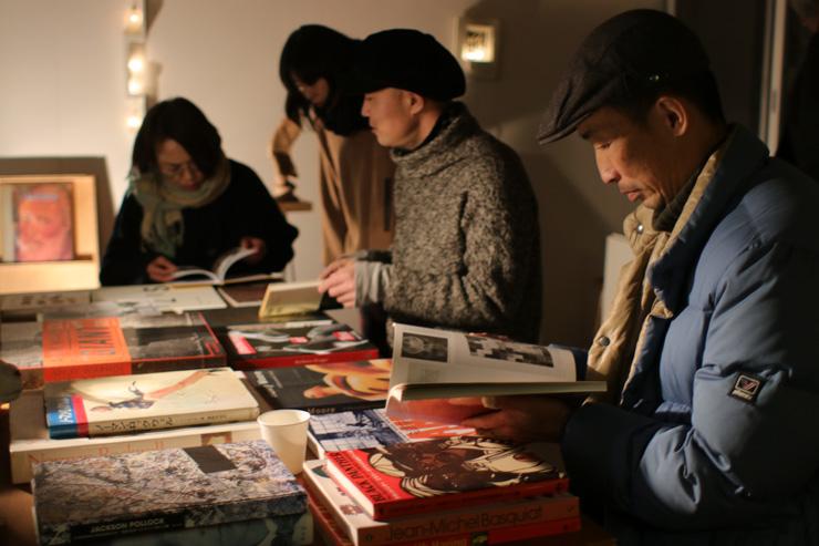 写真右端がこの回のゲスト、彫刻家の古川潤さん。隣が山田さん。近所の常連さんも訪れ、それぞれが気になる写真や本を手に、あれこれ語り合いながらページをめくっていく。