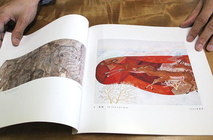 動物を中心に描いていた時期の画集を広げる坂本さん