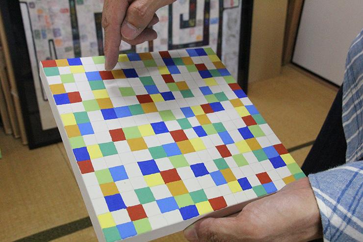 白い画面にフリーハンドで縦横に線を引き、できた形に岩絵具を塗っていく