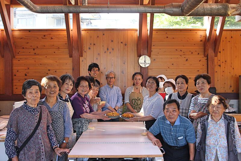 お菓子作り教室で完成したリンゴタルトを手に調理室で撮影した集合写真