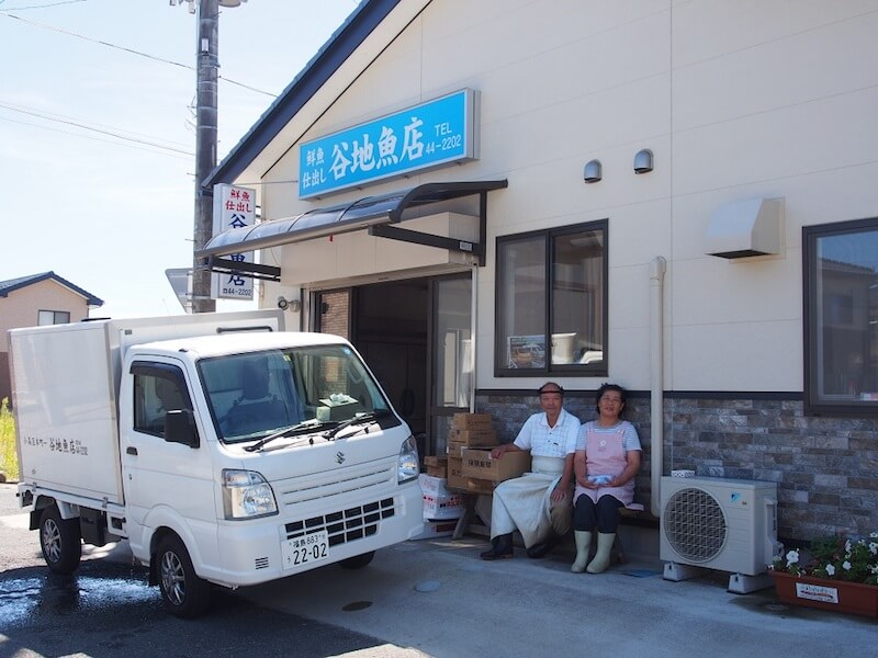 お店の前で谷地さんご夫妻。谷地さんはこのトラックに乗って仮設住宅を巡った